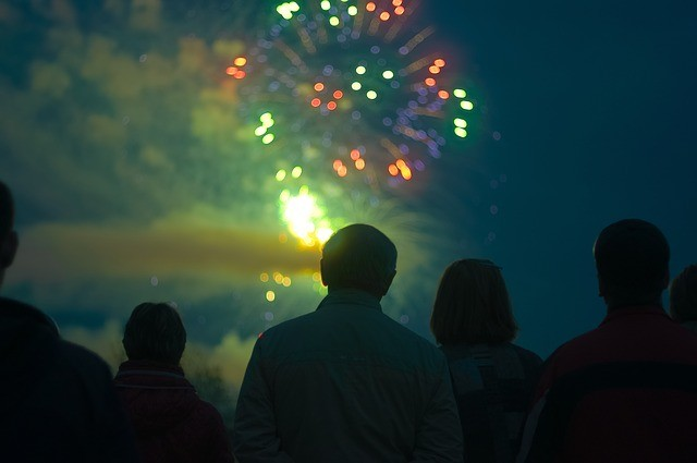 people watching fireworks on an artificial lawn